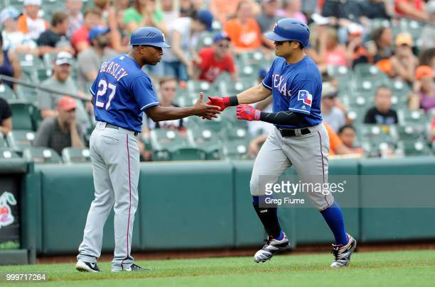 ShinSoo Choo of the Texas Rangers celebrates with third base coach Tony Beasley after hitting a home run in the seventh inning against the Baltimore...