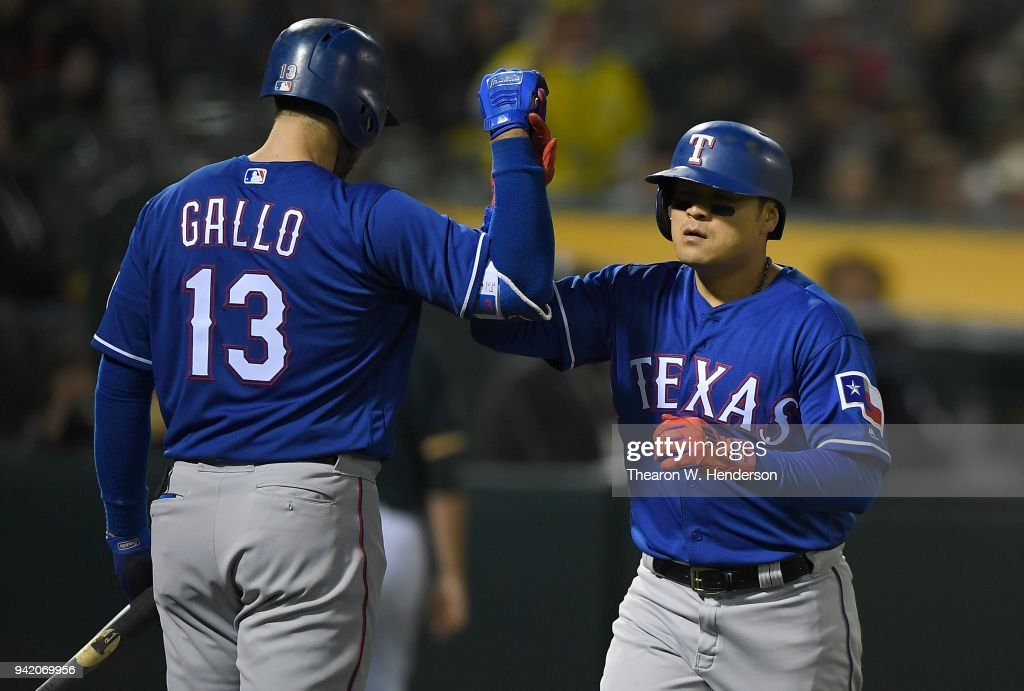 Shin-Soo Choo #17 of the Texas Rangers is congratulated by Joey Gallo #13 after Choo hit a solo home run against the Oakland Athletics in the top of the ninth inning at the Oakland Alameda Coliseum on April 4, 2018 in Oakland, California.