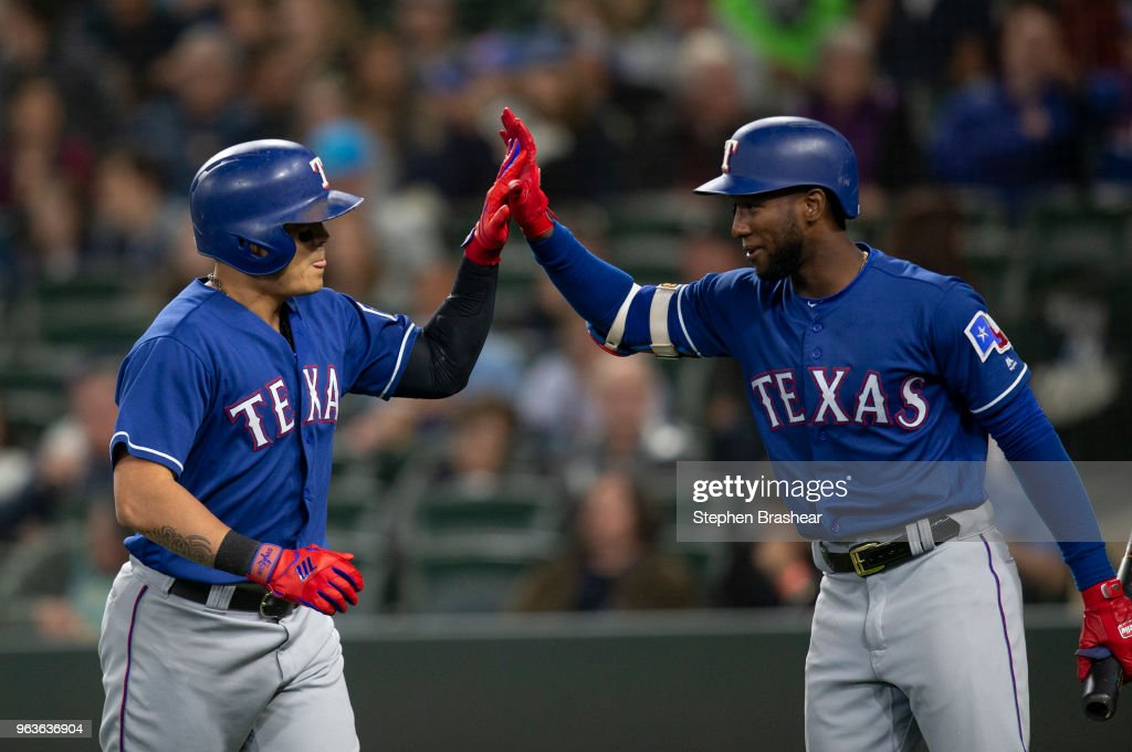 Shin-Soo Choo #17 (L) of the Texas Rangers is congratulated by Jurickson Profar #19 after hitting a solo home run off of starting pitcher Felix Hernandez of the Seattle Mariners during the first inning of a game at Safeco Field on May 29, 2018 in Seattle, Washington.