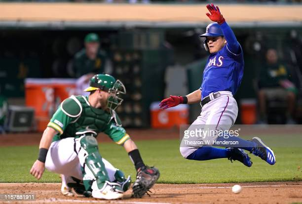 ShinSoo Choo of the Texas Rangers scores as catcher Chris Herrmann of the Oakland Athletics can't hold on to the ball in the top of the fourth inning...