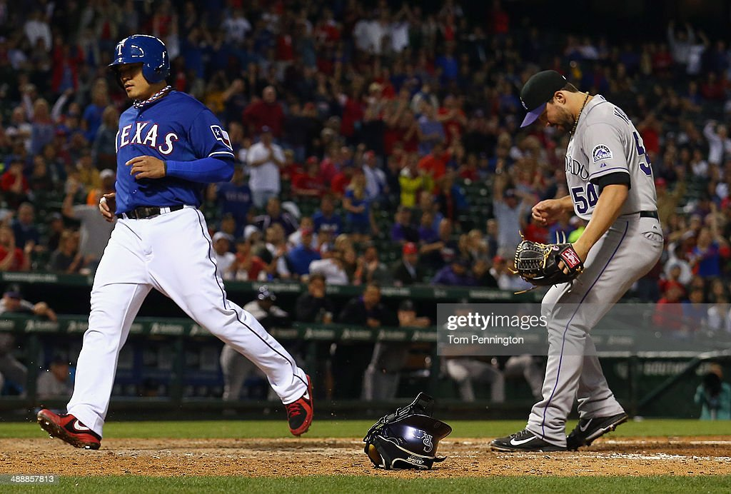 Shin-Soo Choo #17 of the Texas Rangers scores on a wild pitch thrown by Tommy Kahnle #54 of the Colorado Rockies in the bottom of the seventh inning at Globe Life Park in Arlington on May 8, 2014 in Arlington, Texas.