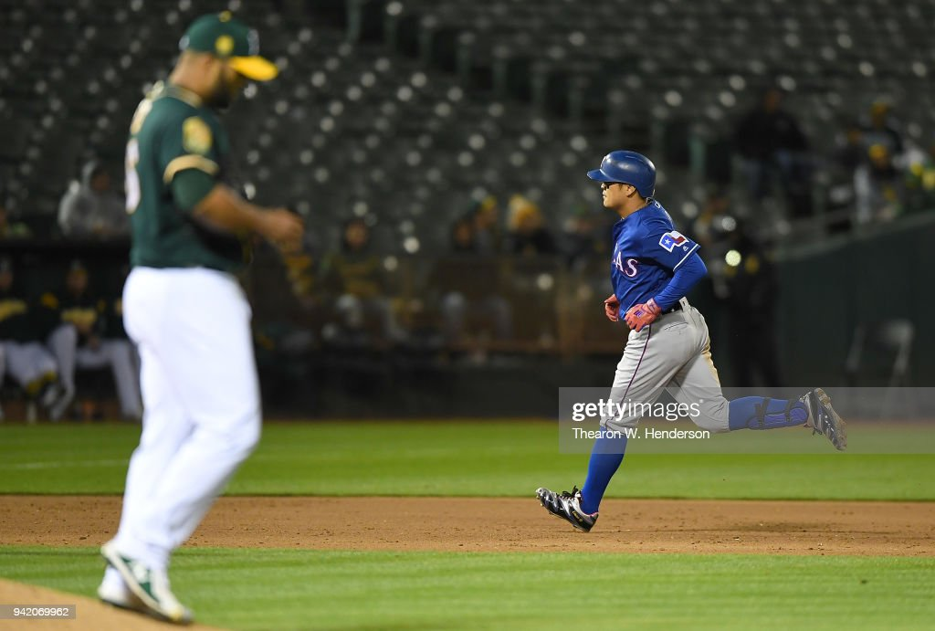 Shin-Soo Choo #17 of the Texas Rangers trots around the bases after hitting a solo home run off of Yusmeiro Petit #36 of the Oakland Athletics in the top of the ninth inning at the Oakland Alameda Coliseum on April 4, 2018 in Oakland, California. The Athletics won the game 6-2.