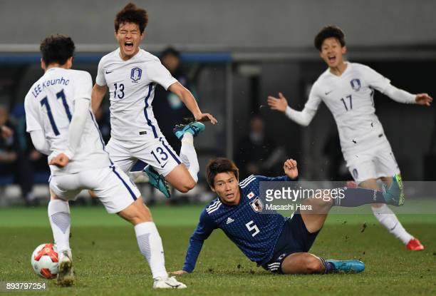 Shintaro Kurumaya of Japan fouls on Ju Sejong of South Korea resulting in the yellow card during the EAFF E1 Men's Football Championship between...
