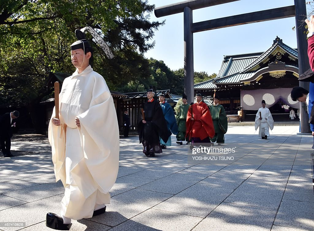 A Shinto priest (L) leads a group of imperial envoy (C) as they leave the controversial Yasukuni shrine in Tokyo as Japanese Emperor Akihito presents an offering to the shrine for the shrine's autumn festival on October 18, 2014. Two Japanese ministers visited a controversial Tokyo war shrine, becoming the first Cabinet-level minister to join a pilgrimage by 100 lawmakers to the spot condemned by China and Korea as a symbol of Japan's wartime aggression. AFP PHOTO / Yoshikazu TSUNO