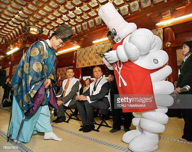 A Shinto priest leads Michelin mascot Bibendum to an altar while director of the Michelin Guides JeanLuc Naret and Michelin Japan president Bernard...