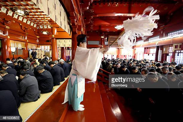 A Shinto priest performs a purification ritual as people pray on the first day of business in 2015 at the Kanda Myojin shrine in Tokyo Japan on...