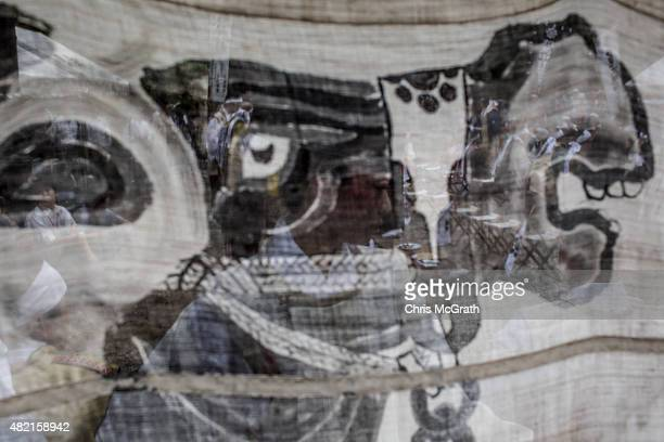 Shinto Priestess is seen through a Samurai banner during a Samurai ritual at Nakamura Shrine on July 24, 2015 in Soma, Japan. Every summer the people...