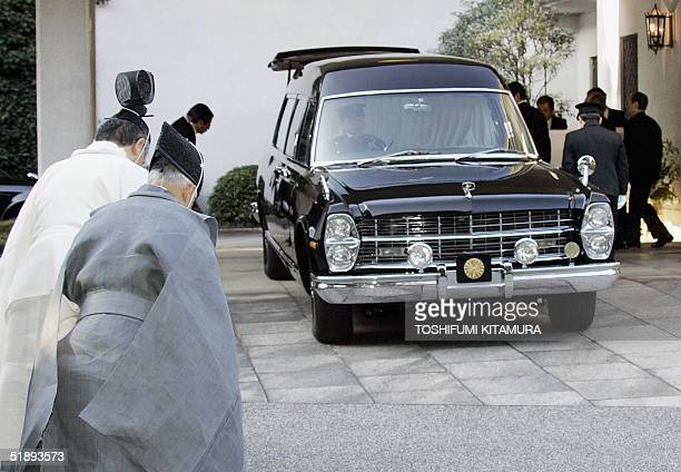 Shinto priests bow while the coffin of late Princess Kikuko is carried into a royal hearse for the funeral ceremony at her residence in Tokyo 26...
