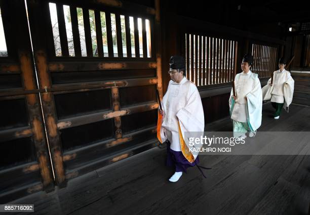 Shinto priests walk in a corridor at the controversial Yasukuni shrine in Tokyo on December 5 2017 Dozens of Japanese parliament members on December...