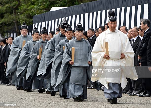 Shinto priests walks at the Imperial Graveyard of Toshimagaoka during the funeral of the late Prince Tomohito in Tokyo June 14 2012 Prince Tomohito...