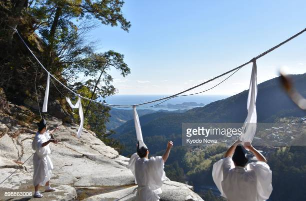 Shinto shrine priests at Kumano Nachi Taisha in Wakayama Prefecture on Dec 27 2017 replace a large 'shimenawa' straw rope with new one ahead of New...