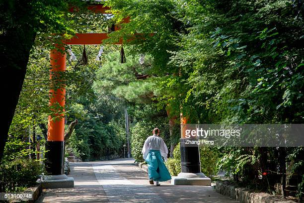 Shinto staff walks under a Torii. Torii to the Ujigami Shrine. Ujigami Shrine, a Shinto shrine in the city of Uji in Kyoto. In 1994, it was...