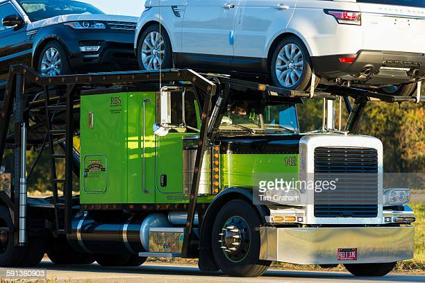 Shiny American Freightliner truck transporting Range Rover autos car transporter on route Interstate 10 Louisiana USA