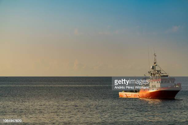 shiny and calm atlantic ocean with red lonely trawler - romatic scene - fishing boat stock pictures, royalty-free photos & images
