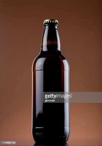 Shiny beer bottle on a tan background