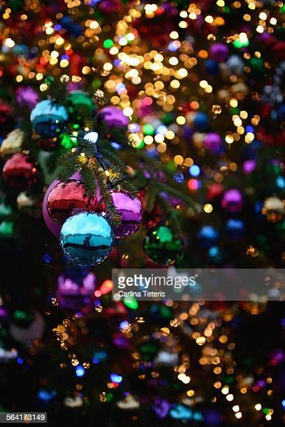 Shiny Christmas balls on and lights on a tree