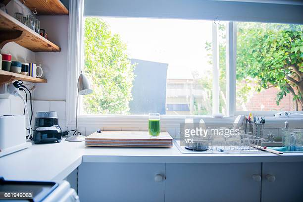 A shiny clean kitchen and green smoothy.