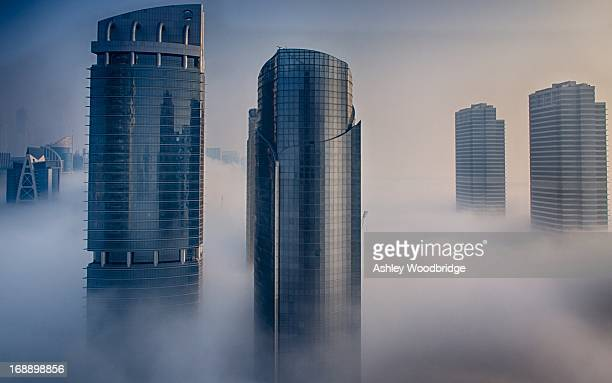 Shiny commercial high rises/skyscrapers reaching through early morning January fog in JLT -Dubai .
