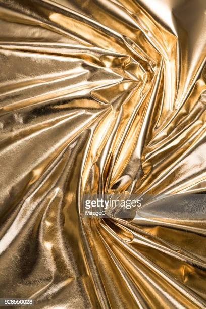 shiny gold colored textile texture - metallic look stock-fotos und bilder