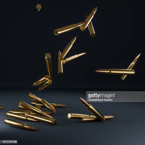 shiny metal rifle bullets falling down over dark background. - gun control stock pictures, royalty-free photos & images