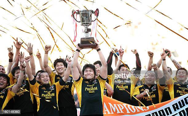 Shinya Makabe of Suntory celebrates with the cup and his teammates after victory in the Japan Rugby Top League playoff final match between Suntory...
