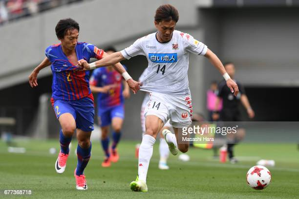 Shinya Uehara of Consadole Sapporo and Sei Muroya of FC Tokyo compete for the ball during the J.League Levain Cup Group A match between FC Tokyo and...