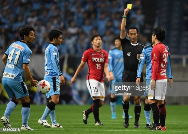 Shinya Yajima of Urawa Red Diamonds is shown a yellow card by referee Hajime Matsuo during the JLeague J1 match between Urawa Red Diamonds and...