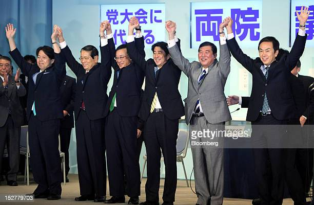 Shinzo Abe Japan's former prime minister and newly elected president of the Liberal Democratic Party third from right raises his hands with other...