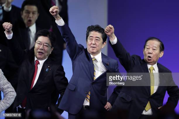 Shinzo Abe Japan's prime minister and president of the Liberal Democratic Party center raises his fist with Katsunobu Kato chairman of the general...