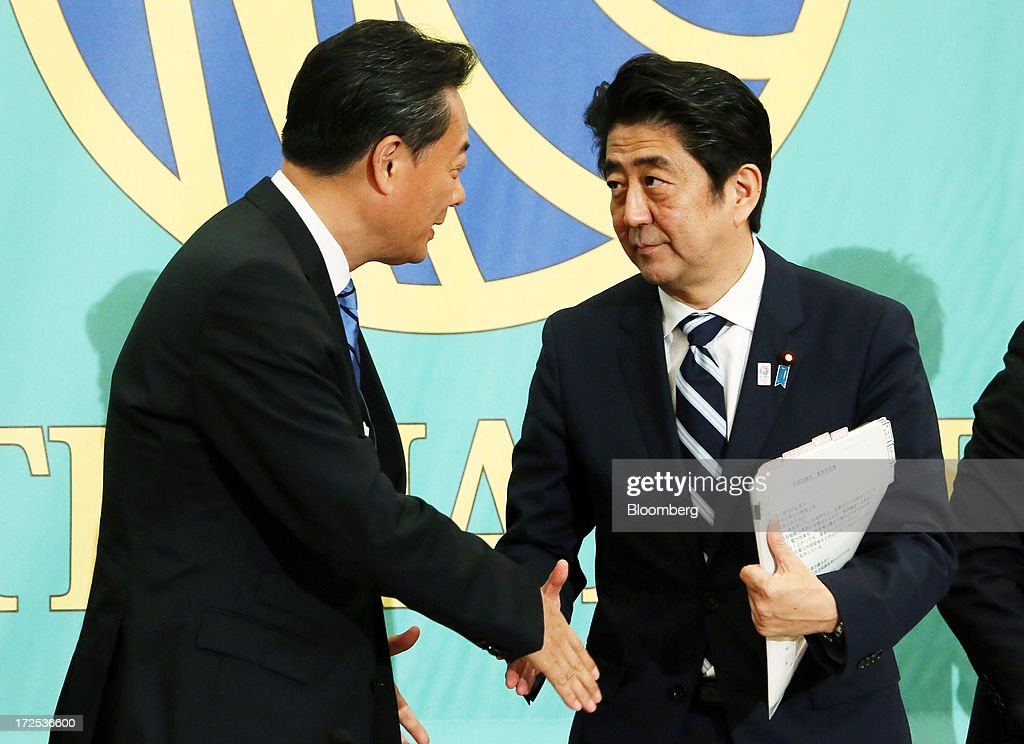 Shinzo Abe, Japan's prime minister and president of the Liberal Democratic Party (LDP), right, shakes hands with Banri Kaieda, president of the Democratic Party of Japan (DPJ), following a debate at the Japan National Press Club in Tokyo, Japan, on Wednesday, July 3, 2013. Abe called for laws, not force-based order, in the Asia region during a televised debate with leaders of other political parties in Tokyo today ahead of the July 21 upper house election. Photographer: Haruyoshi Yamaguchi/Bloomberg via Getty Images
