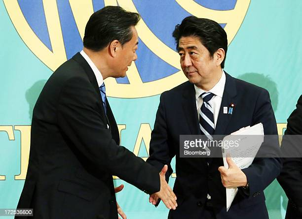 Shinzo Abe Japan's prime minister and president of the Liberal Democratic Party right shakes hands with Banri Kaieda president of the Democratic...