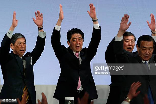 Shinzo Abe Japan's prime minister and president of the Liberal Democratic Party center cheers with Masahiko Komura vice president left Shigeru Ishiba...