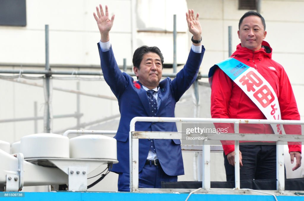 Shinzo Abe, Japans prime minister and president of the Liberal Democratic Party (LDP), center, waves as he stands next to Yoshiaki Wada, a member of the House of Representatives, during an election campaign rally in Sapporo, Hokkaido, on Sunday, Oct. 15, 2017. Abe looked set to retain his coalitions dominant position in parliament after the Oct. 22 general election, according to a series of large opinion surveys carried out by domestic media. Photographer: Eiji Ohashi/Bloomberg via Getty Images