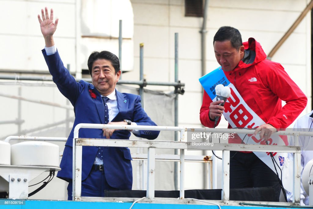 Shinzo Abe, Japans prime minister and president of the Liberal Democratic Party (LDP), left, waves as he stands next to Yoshiaki Wada, a member of the House of Representatives, during an election campaign rally in Sapporo, Hokkaido, on Sunday, Oct. 15, 2017. Abe looked set to retain his coalitions dominant position in parliament after the Oct. 22 general election, according to a series of large opinion surveys carried out by domestic media. Photographer: Eiji Ohashi/Bloomberg via Getty Images
