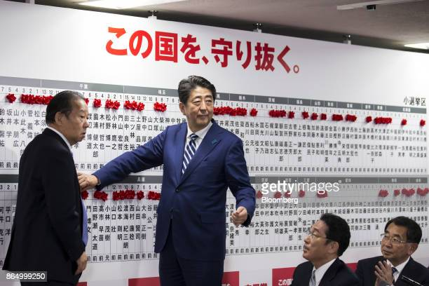 Shinzo Abe Japan's prime minister and president of the Liberal Democratic Party center places a red paper rose on a LDP candidate's name to indicate...