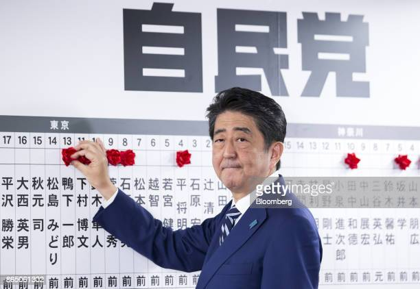 Shinzo Abe Japan's prime minister and president of the Liberal Democratic Party places a red paper rose on a LDP candidate's name to indicate an...