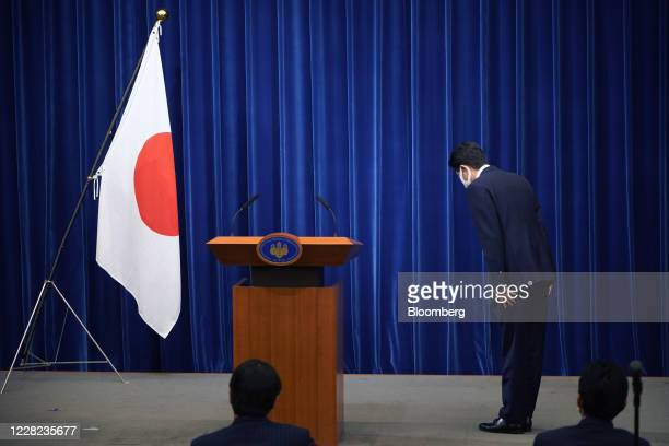 Shinzo Abe, Japan's prime minister, bows to a Japanese national flag as he arrives for a news conference in Tokyo, Japan, on Friday, Aug. 28, 2020....