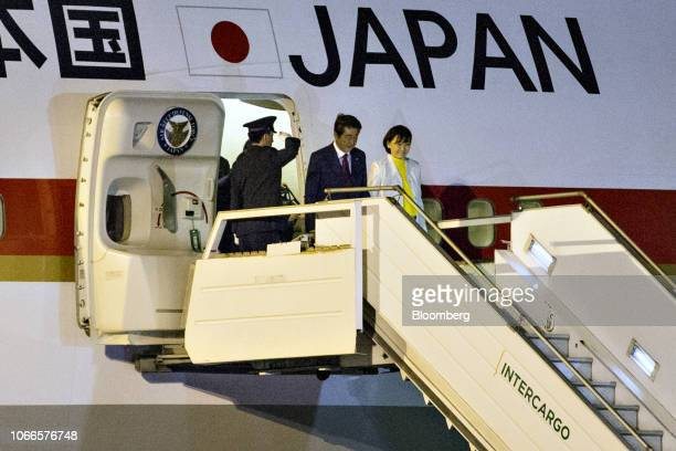Shinzo Abe Japan's prime minister center and his wife Akie Abe right disembark a plane after arriving at Ezeiza Airport ahead of the G20 Leaders'...