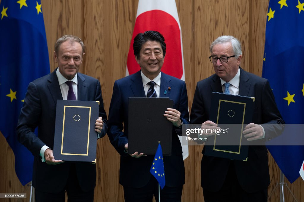 Shinzo Abe, Japan's prime minister, center, Donald Tusk, president of the European Union (EU), left, and Jean-Claude Juncker, president of the European Commission, left, pose for photographs during a contract signing ceremony during a summit at the prime minister's official residence in Tokyo, Japan, on Tuesday, July 17, 2018. Japan and the EU signed a trade agreement on Tuesday in Tokyo that lowers barriers on the movement of goods and services between the two economies and provides a counterweight to U.S. protectionism. Photographer: Martin Bureau/Pool via Bloomberg
