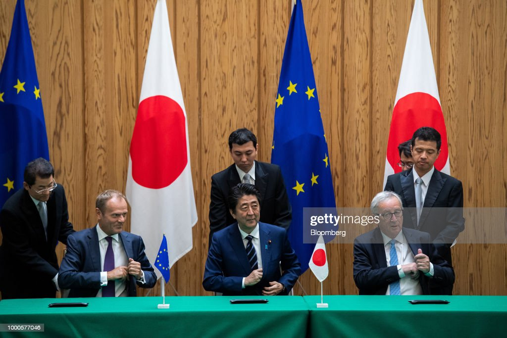 Shinzo Abe, Japan's prime minister, center, Donald Tusk, president of the European Union (EU), left, and Jean-Claude Juncker, president of the European Commission, left, sit during a contract signing ceremony during a summit at the prime minister's official residence in Tokyo, Japan, on Tuesday, July 17, 2018. Japan and the EU signed a trade agreement on Tuesday in Tokyo that lowers barriers on the movement of goods and services between the two economies and provides a counterweight to U.S. protectionism. Photographer: Martin Bureau/Pool via Bloomberg