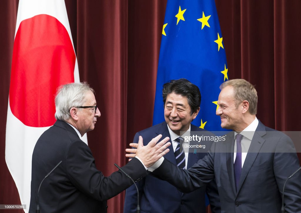 Shinzo Abe, Japan's prime minister, center, reacts as Jean-Claude Juncker, president of the European Commission, left, and Donald Tusk, president of the European Union (EU), shake hands during a joint news conference following a summit at the prime minister's official residence in Tokyo, Japan, on Tuesday, July 17, 2018. Japan and the EU signed a trade agreement on Tuesday in Tokyo that lowers barriers on the movement of goods and services between the two economies and provides a counterweight to U.S. protectionism. Photographer: Tomohiro Ohsumi/Bloomberg via Getty Images