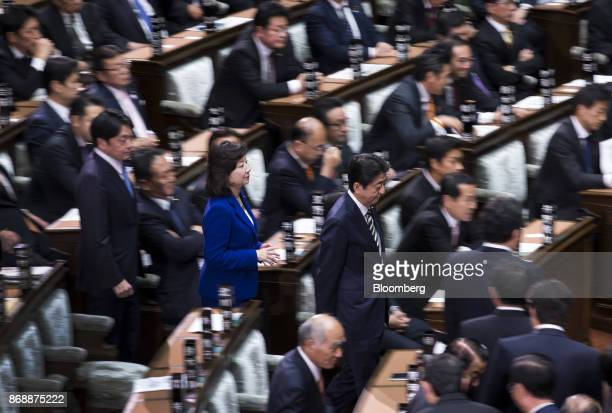 Shinzo Abe Japan's prime minister center right and Seiko Noda Japan's internal affairs and communications minister center left make their way to cast...