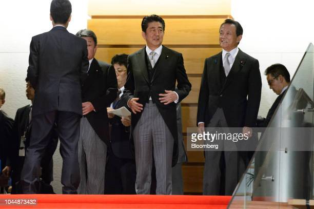 Shinzo Abe Japan's prime minister center speaks with Taro Aso deputy prime minister and finance minister right before posing for a group photograph...