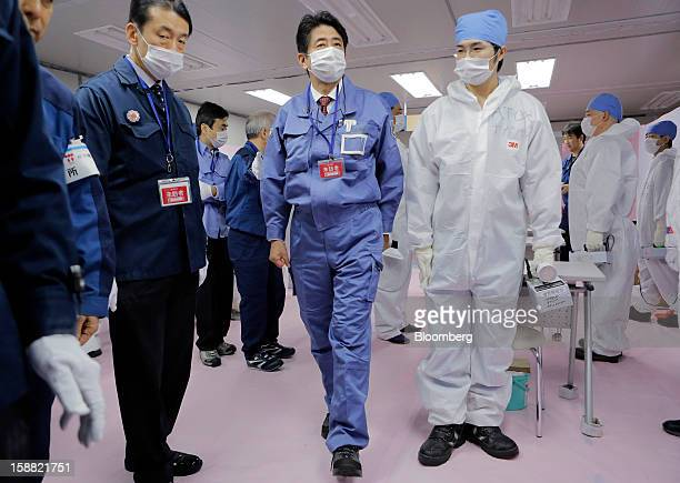 Shinzo Abe Japan's prime minister center walks through the emergency operations center at Tokyo Electric Power Co's Fukushima DaiIchi nuclear power...