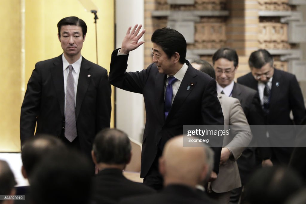 Shinzo Abe, Japan's prime minister, center, waves as he leaves an event hosted by the Research Institute of Japan in Tokyo, Japan, on Tuesday, Dec. 19, 2017. Abe said he wants take ties with China to a new level. Photographer: Kiyoshi Ota/Bloomberg via Getty Images