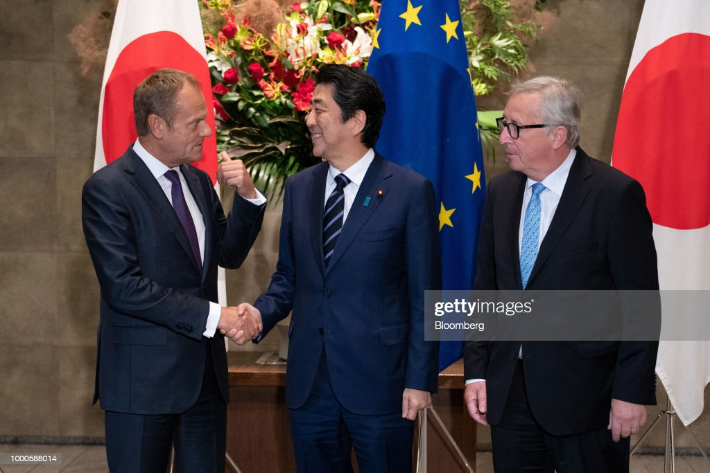 Shinzo Abe, Japan's prime minister, center, welcomes Donald Tusk, president of the European Union (EU), left, and Jean-Claude Juncker, president of the European Commission, left, for a summit at the prime minister's official residence in Tokyo, Japan, on Tuesday, July 17, 2018. Japan and the EU signed a trade agreement on Tuesday in Tokyo that lowers barriers on the movement of goods and services between the two economies and provides a counterweight to U.S. protectionism. Photographer: Martin Bureau/Pool via Bloomberg