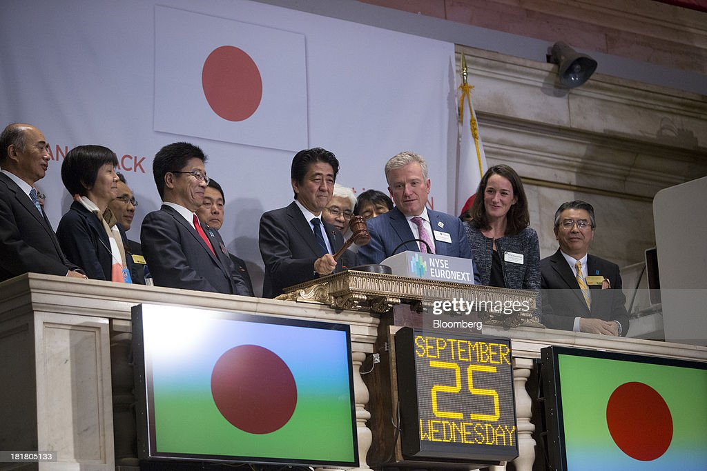 Shinzo Abe, Japan's prime minister, fourth from left, rings the closing bell at the New York Stock Exchange (NYSE) in New York, U.S., on Wednesday, Sept. 25, 2013. Abe's pledge to end 15 years of deflation and the Bank of Japan's monetary policy easing, along with Tokyo's winning bid to host the 2020 Olympic Games have helped boost consumer sentiment. Photographer: Scott Eells/Bloomberg via Getty Images