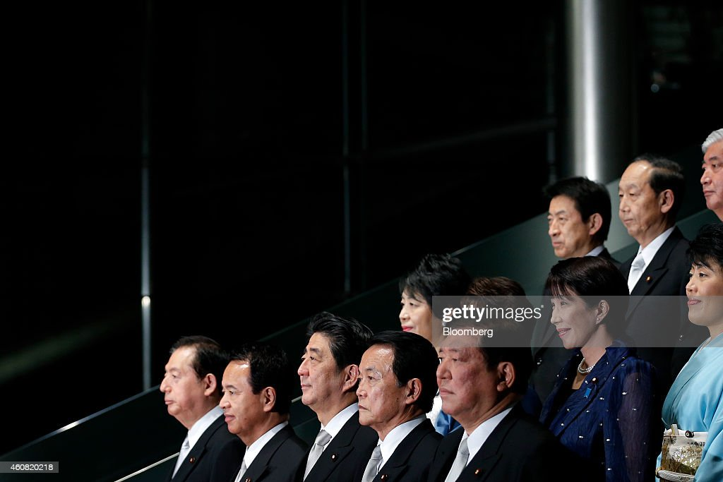 Shinzo Abe, Japan's prime minister, front row center, poses for a group photograph with members of his new cabinet including Akihiro Ohta, re-appointed land, infrastructure, and transport minister, front row left, Akira Amari, re-appointed economic revitalization minister, front row second left, Taro Aso, re-appointed deputy prime minister and minister for finance and financial services, front row second right, and Shigeru Ishiba, re-appointed minister in charge of regional economy, front row right, at the prime minister's official residence in Tokyo, Japan, on Wednesday, Dec. 24, 2014. Abe appointed a former soldier and security veteran as his new defense minister, as he prepares to push through legislation to toughen the countrys military stance amid a dispute with China. Photographer: Kiyoshi Ota/Bloomberg via Getty Images