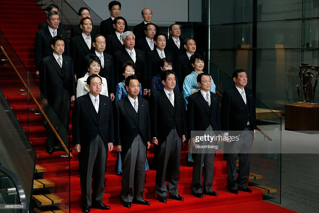 Shinzo Abe, Japan's prime minister, front row center, poses for a group photograph with his new cabinet members at the prime minister's official residence in Tokyo, Japan, on Wednesday, Dec. 24, 2014. Abe appointed a former soldier and security veteran as his new defense minister, as he prepares to push through legislation to toughen the countrys military stance amid a dispute with China. Photographer: Kiyoshi Ota/Bloomberg via Getty Images