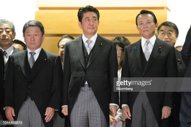Shinzo Abe Japan's prime minister front row center stands with Taro Aso deputy prime minister and finance minister right and Toshimitsu Motegi...